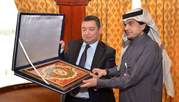 Hikmatullozoda presents a souvenir to al-Shaibei following his meeting with the QIIB chief executive