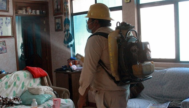 A Health Ministry employee fumigates a home against the Aedes aegypti mosquito to prevent the spread