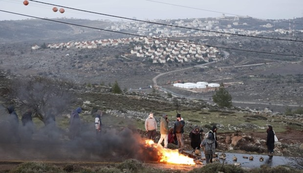 Jewish settlers set tyres as Israeli security forces are preparing to evict the occupants