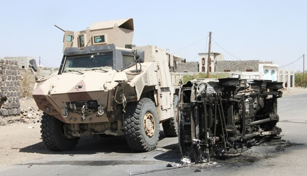 Fighters loyal to the Saudi-backed Yemeni president drive an armoured vehicle