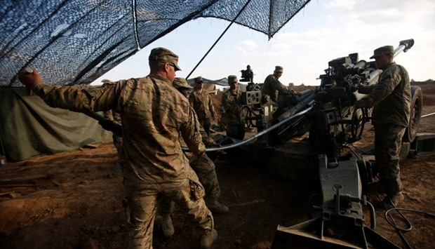 US soldiers from the 2nd Brigade, 82nd Airborne Division clean the barrel of artillery at a military