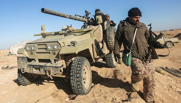 Fighters of the Hashed al-Shaabi paramilitaries sit in a heavily-armed vehicle near the frontline vi
