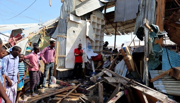 Traders look at a stall destroyed at the scene of a suicide bomb explosion at the Wadajir market in