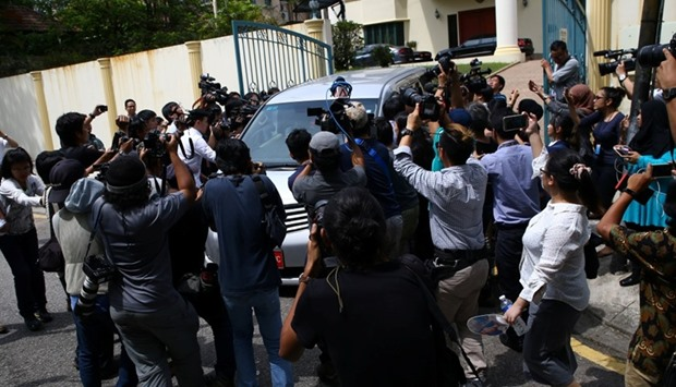 Members of the media surround a North Korea official's car as it leaves the North Korea embassy in K