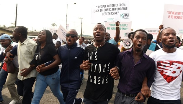 Protesters hold placards and shout slogans during an anti-government demonstration in Lagos