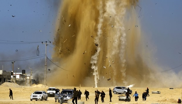 Palestinians run for cover as smoke rises following an Israeli air strike on a Hamas post, in the no