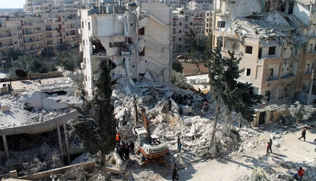 Syrian men and Civil Defence volunteers search for survivors following an air strike in Idlib.