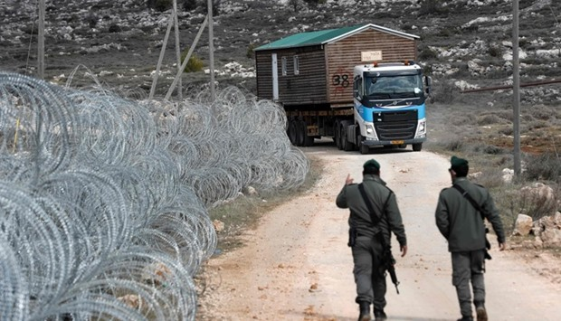 A prefabricated house is transported by a lorry after being are removed from the Israeli Amona