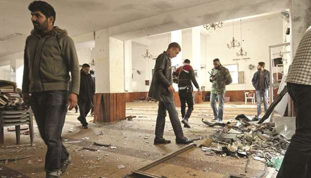 Libyans inspect the interior of a mosque in Benghazi, after it was hit with a twin bomb attack.