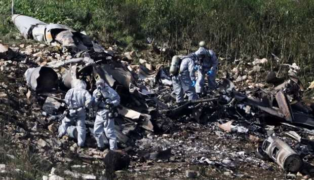 Israeli security forces examine the remains of an F-16 Israeli war plane near the village of Harduf,
