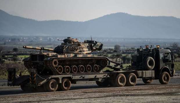 A Turkish military truck carries a tank as it is dispatched to the border in Hatay, near the Turkey-