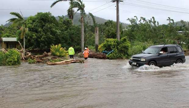 A car passing through a flooded street as Red Cross workers check on a house in the Apia area