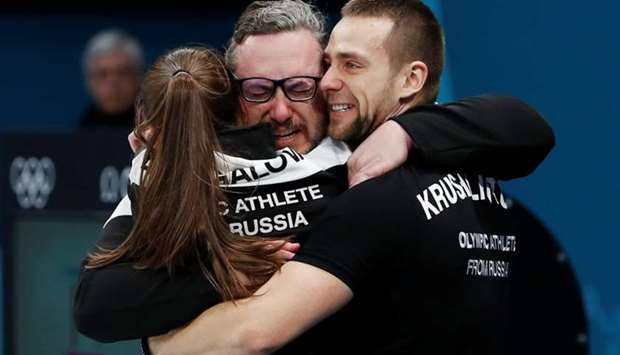 Aleksandr Krushelnitckii and Anastasia Bryzgalova, Olympic athletes from Russia, hug their coach Vas