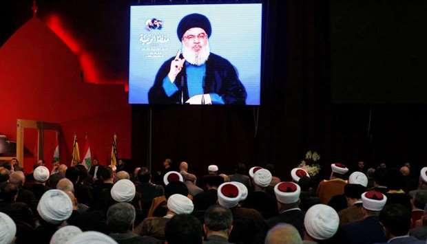Lebanon's Hezbollah leader Sayyed Hassan Nasrallah is seen on a video screen as he addresses his sup