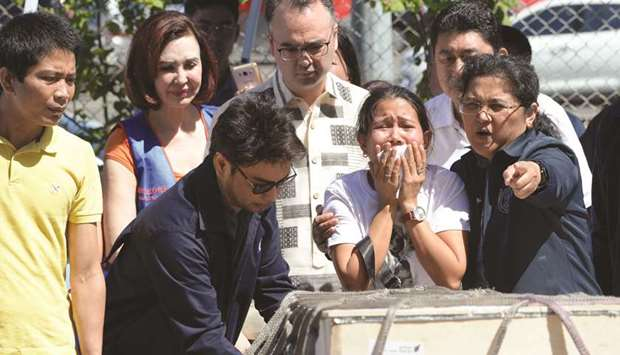 Jessica (second right), sister of Filipina overseas worker Joanna Demafelis, cries in front of a woo