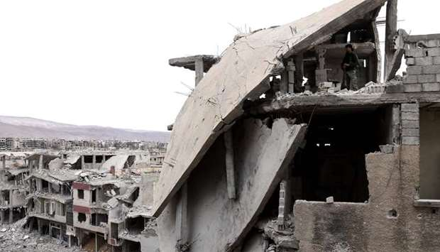 A Syrian fighter take a position on top of a damaged building on the frontline in the rebel-held enc