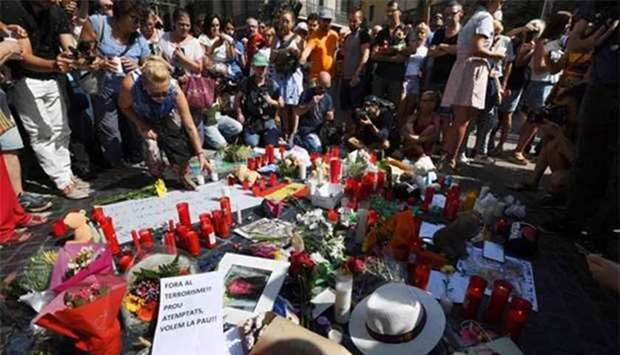 People stand next to flowers, candles and signs set up on the Las Ramblas boulevard in Barcelona as