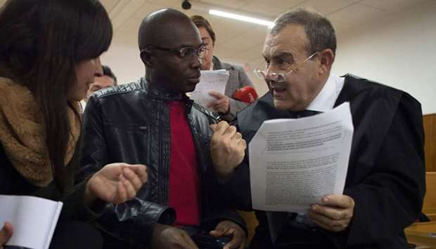 Ali Ouattara, 45 (C) talk with his lawyer Juan Isidro Fernandez (R) in court during his trial in Ceu
