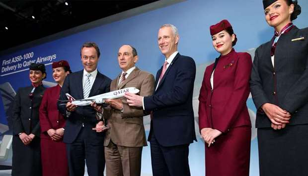 Al-Baker with Brégier and Chorleton holding a scale model of world's first Airbus A350-1000 in Qatar