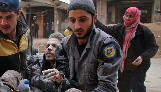 Civil Defence volunteers, known as the White Helmets, carry a wounded man into a makeshift hospital