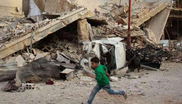 A Syrian boy runs past a destroyed building during air strikes by regime forces in the rebel-held to