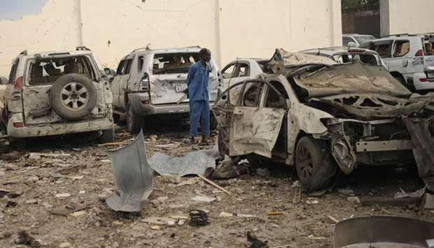 A Somali man stands in the middle of the wreckages of cars as he looks at the scene of a suicide car