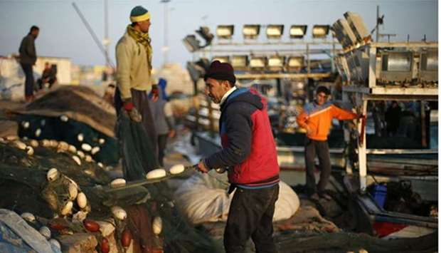 Palestinian fishermen clean their net at the Seaport of Gaza City.