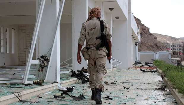 A fighter from the separatist Southern Transitional Council gather at the site of two suicide car bo