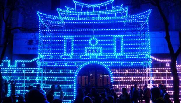 Visitors walking past an ancient gate lit up with LED lights during the start of the Lantern Festiva
