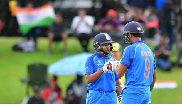 India's Manjot Kalra (R) celebrates after hitting a four with teammate Prithvi Shaw (R) during the U