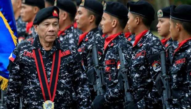 Philippine President Rodrigo Duterte, wearing a military uniform, reviews scout ranger troops