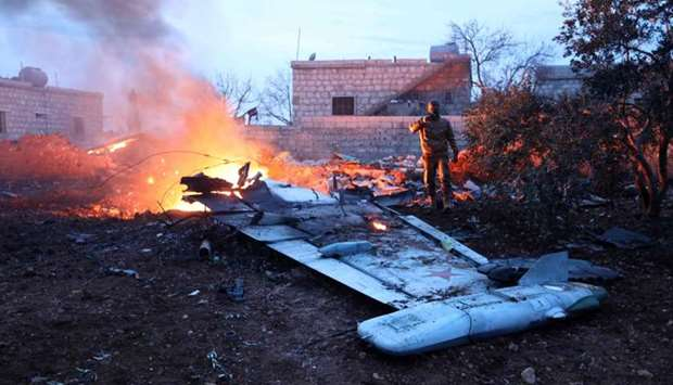 A picture taken on February 3, 2018, shows a Rebel fighter taking a picture of a downed Sukhoi-25 fi