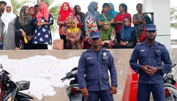 Maldivian Police officers stand guard near the MDP (Maldives Democratic Party) opposition party head