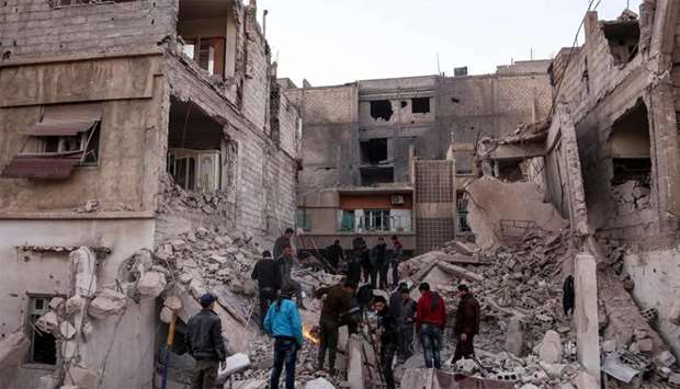 Syrian civil defence volunteers and other civilians attempt to remove rubble from the site of a coll