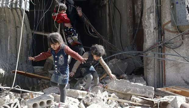 Children walk on rubble of damaged buildings after an airstrike in the besieged town of Douma in eas