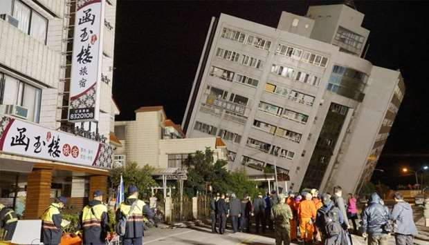 Rescue workers block off the area to search for survivors outside a building which tilted to one sid