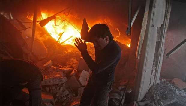A Syrian man searches for people in a fire following regime air strikes on the rebel-held besieged t