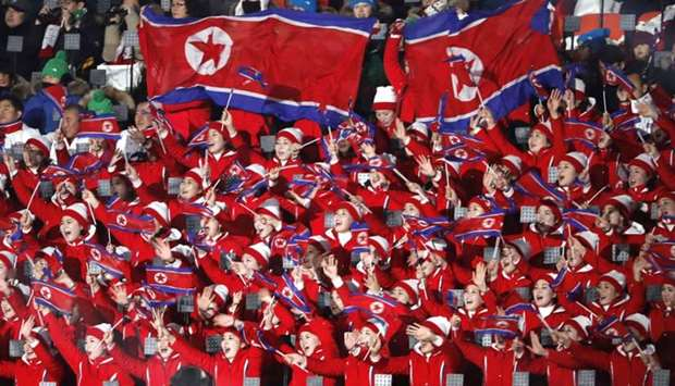 Cheerleaders of North Korea wave their national flags as they wait the start of the opening ceremony