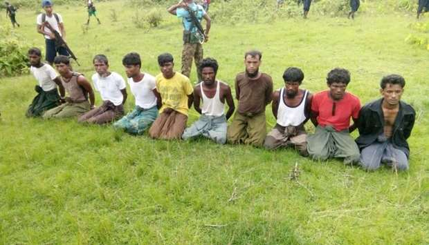 Ten Rohingya Muslim men with their hands bound kneel as members of the Myanmar security forces stand