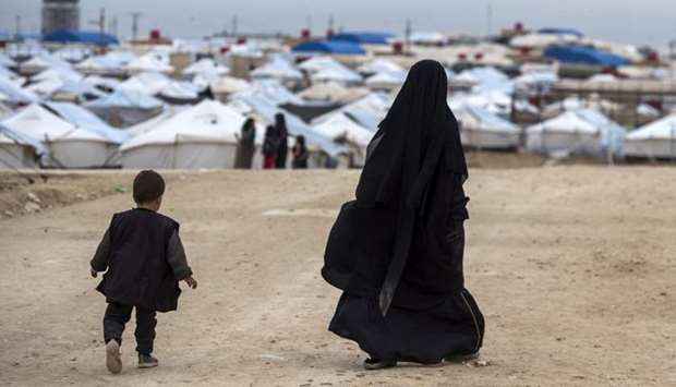 A displaced Syrian woman and a child walk toward tents at a camp of al-Hol in al-Hasakeh governorate