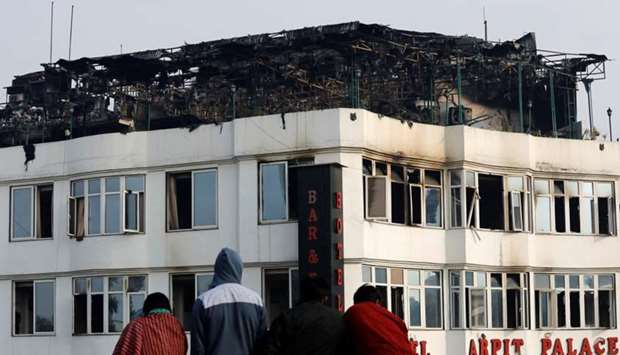 Onlookers stand on the rooftop of a building as they look at a hotel where a fire broke out in New D