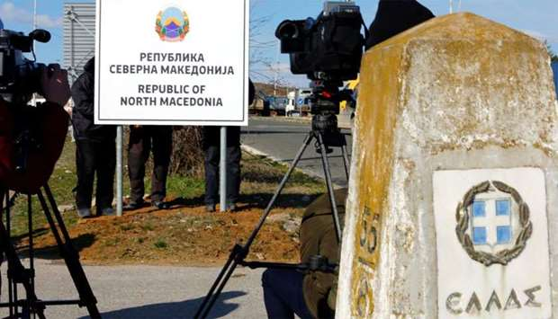 Workers set up a sign with Macedonia's new name at the border between Macedonia and Greece, near Gev