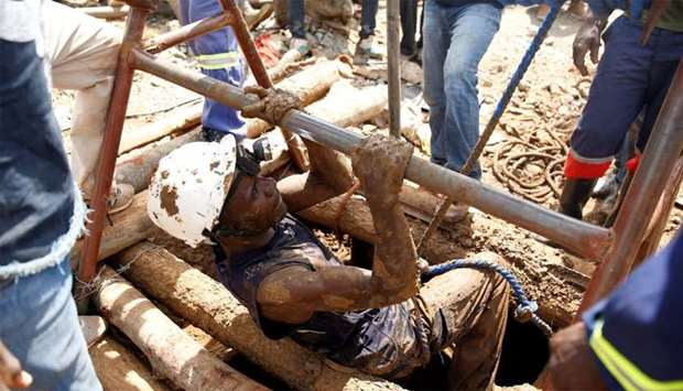 A mine rescuer climbs of a shaft as retrieval efforts proceed for trapped illegal gold miners in Kad