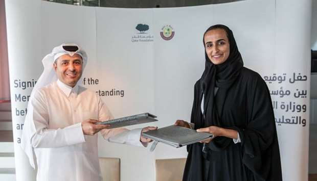 HE Sheikha Hind bint Hamad al-Thani and HE Dr Mohamed Abdul Wahed al-Hammadi exchange the agreement.