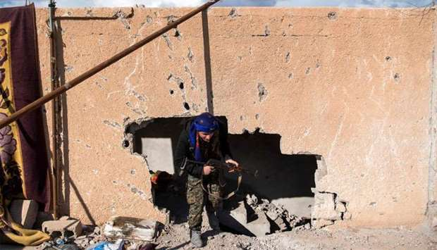 A fighter with the US-backed Syrian Democratic Forces (SDF) goes through a hole in the wall in the f