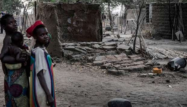 A women and her children stand in front of houses destroyed by a group of herdsmen in Volki, Nigeria