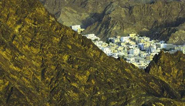 The traditional houses of the old city district sit surrounded by mountains in Muscat