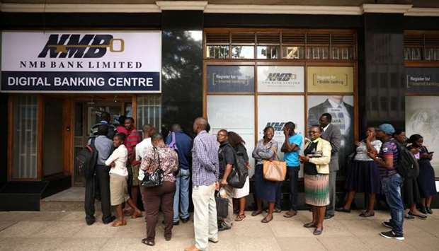 People queue outside a bank in Harare, Zimbabwe