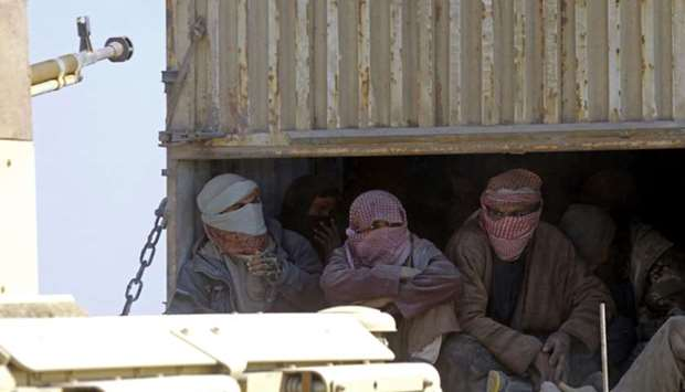 Men, identified as Islamic State group fighters, who surrendered to Kurdish-led Syrian Democratic Fo