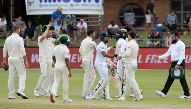 Sri Lanka's Kusal Mendis (C) shakes hands with South African players after matching SA's score to wi